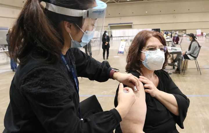 A patient receives a dose of a COVID-19 vaccine at an immunization clinic at the Metro Toronto Convention Centre in Toronto on Jan. 18, 2021.