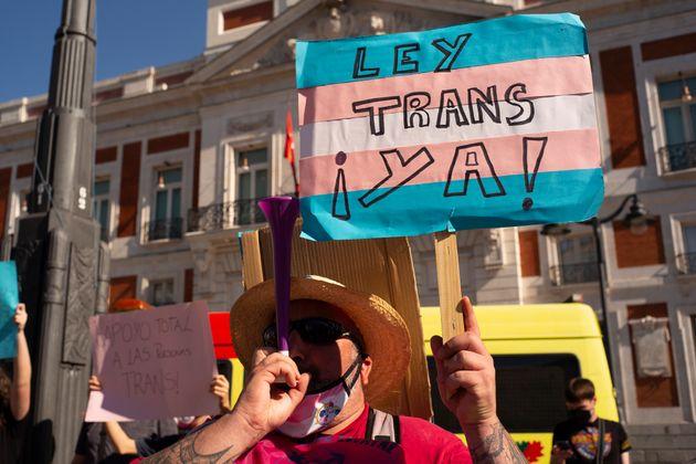 Una persona sujeta una pancarta por la Ley Trans en la puerta del