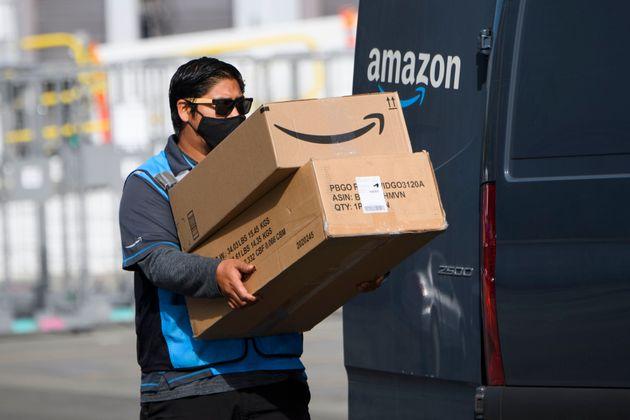 Un repartidor carga su furgoneta con paquetes de Amazon en California