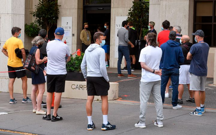 Tennis players queue for a Covid-19 coronavirus test at a hotel in Melbourne on February 4, 2021, as six Australian Open warm-up events were on hold and hundreds of players and officials in isolation as a fresh coronavirus case left organisers scrambling to ensure the Grand Slam tennis tournament goes ahead.