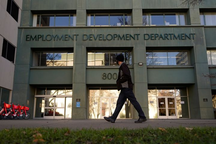 In this Dec. 18, 2020, file photo, a person passes the office of the California Employment Development Department in Sacramen