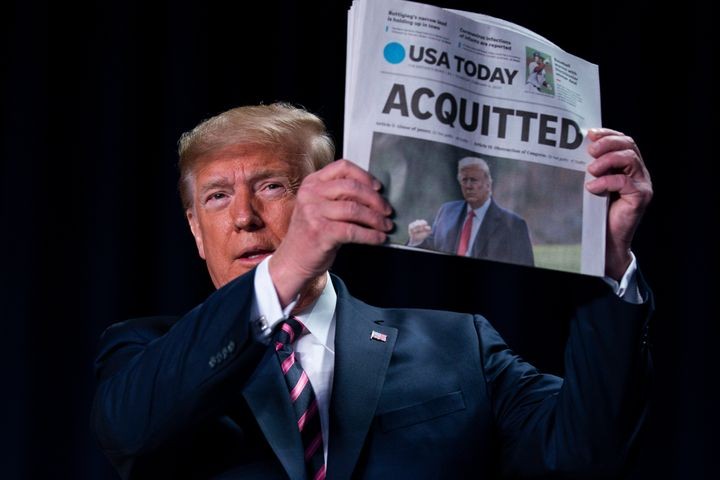 """President Donald Trump holds up a newspaper with the headline that reads """"ACQUITTED"""" at the 68th annual National Prayer Break"""