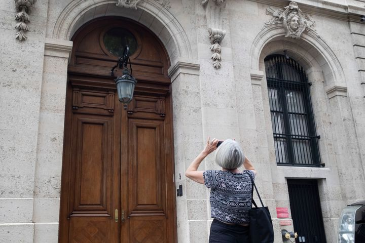 A pedestrian stops to take a photo of Jeffrey Epstein's townhouse on the Upper East Side of Manhattan.The Epstein Victi