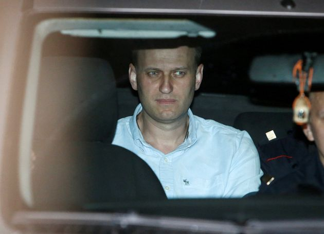 Russian opposition leader Alexei Navalny sits in a police car after being found guilty by a court of...