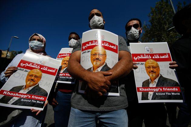 People hold posters of slain Saudi journalist Jamal Kashoggi, near the Saudi Arabia consulate in Istanbul,...