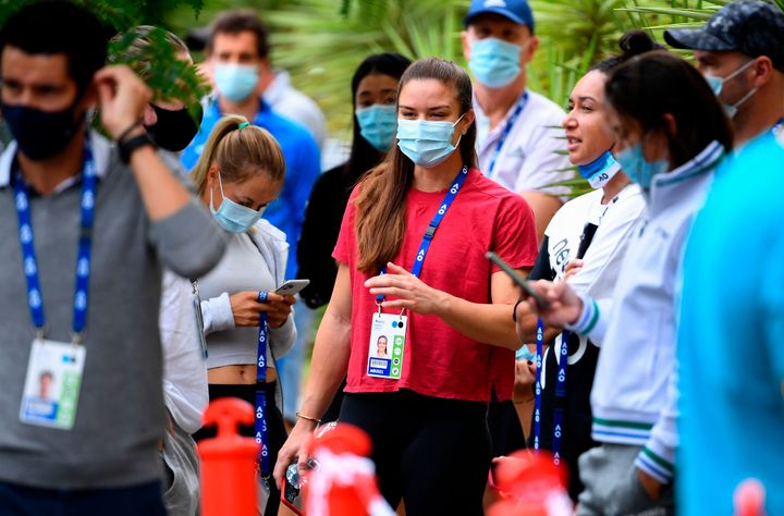 Tennis player Maria Sakkari of Greece (center) waits outside a hotel Thursday for a COVID-19 test in Melbourne.