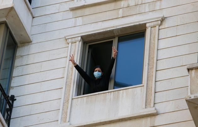 .A woman who is in quarantine gestures from a window at a hotel in
