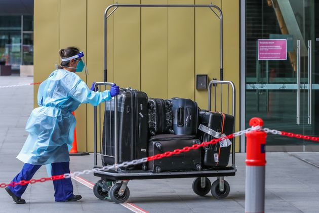 A hotel quarantine staff member is seen wearing full PPE gear while pushing a luggage trolley prior to...