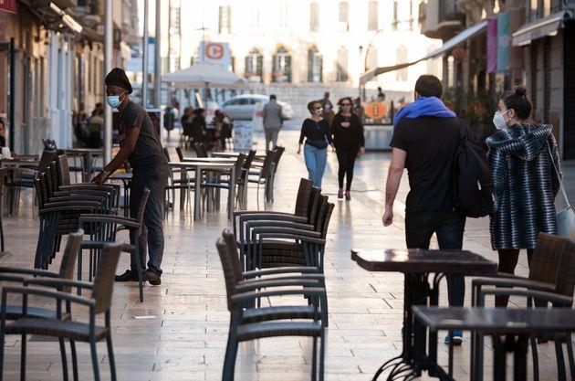 Un trabajador apila sillas en la terraza de un bar de Málaga el 2 de febrero de 2020, mientras...