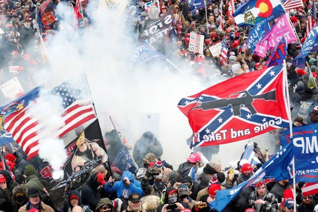 Tear gas is released into a crowd of protesters, with one wielding a Confederate battle flag that reads...