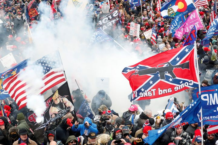 "Tear gas is released into a crowd of protesters, with one wielding a Confederate battle flag that reads ""Come and Take It,"" d"