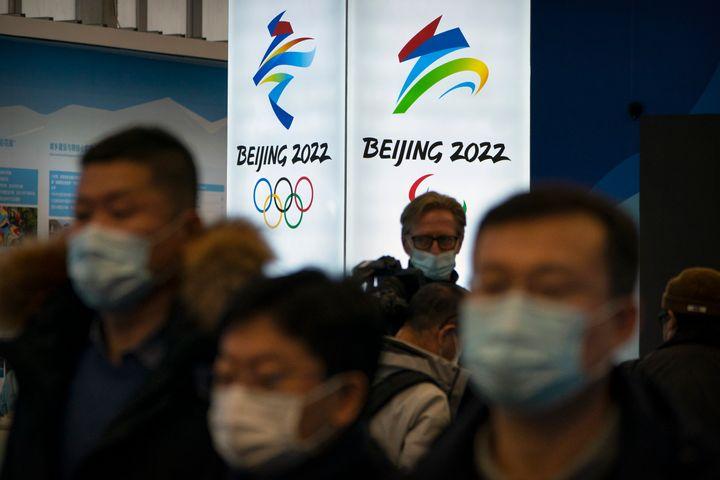 Des visiteurs portant des masques faciaux pour se protéger contre le coronavirus regardent une exposition dans un centre des visiteurs des sites olympiques d'hiver de Yanqing, à la périphérie de Pékin, le vendredi 5 février 2021.