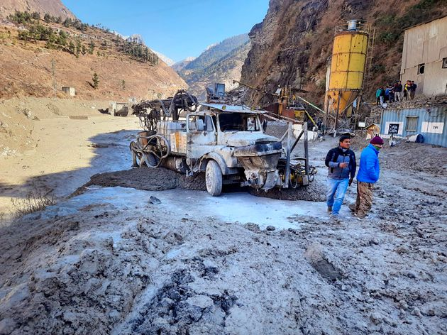 People inspect the site near the damaged Dhauliganga hydropower project at Reni village in Chamoli district...