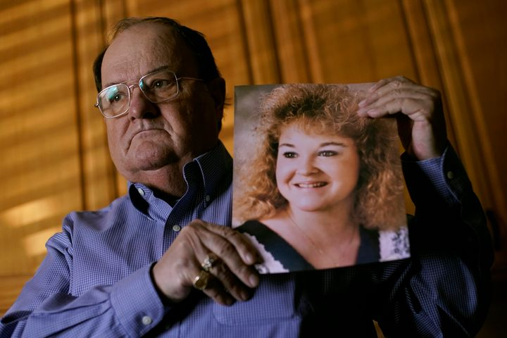 Mortuary owner Brian Simmons holds a photo of his daughter Rhonda Ketchum who died before Christmas of COVID-19, Thursday, Ja