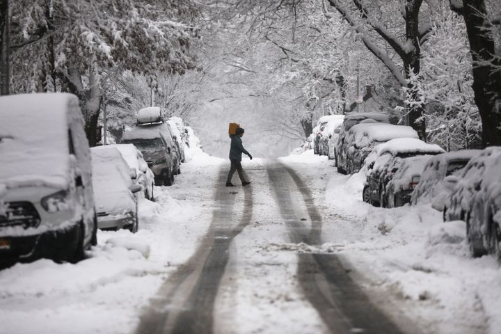 A person walks along the street during a snowstorm in New York City on Sunday. The region is experiencing its second maj