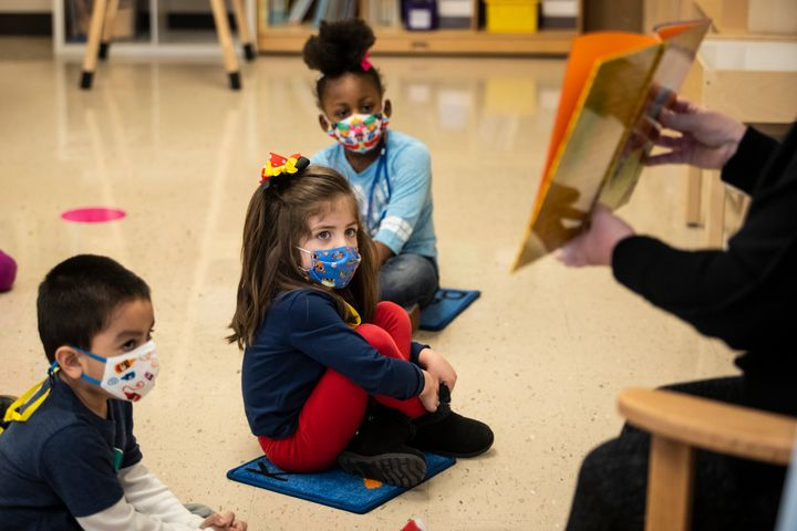 Pre-kindergarten students listen as their teacher reads a story at Dawes Elementary in Chicago, Monday, Jan. 11, 2021. (Ashle