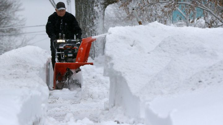A man works to clear a sidewalk after a snowstorm Tuesday in Marlborough, Massachusetts.