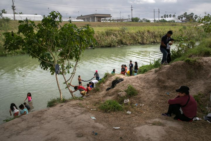 Asylum-seekers wash clothes on the Mexican side of the Rio Grande.