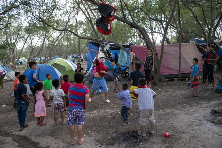 Immigrant children break a birthday pinata at a camp for asylum-seekers on Dec. 9, 2019, in Matamoros.