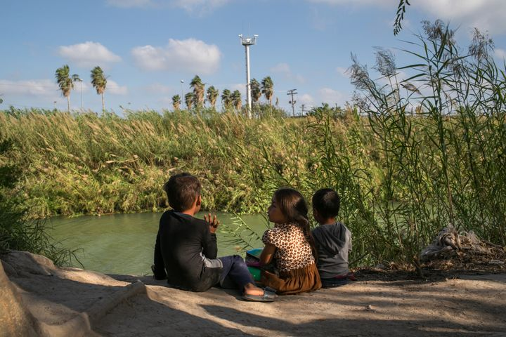Young Central American asylum-seekers sit on the bank of the Rio Grande, as cameras from an American surveillance tower look