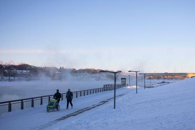 Pedestrians walk by River Landing on the South Saskatchewan River during an extreme cold warning in Saskatoon,...