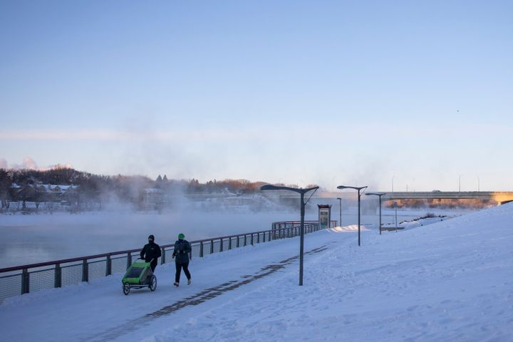 Pedestrians walk by River Landing on the South Saskatchewan River during an extreme cold warning in Saskatoon, Sask. on Feb. 5, 2021.