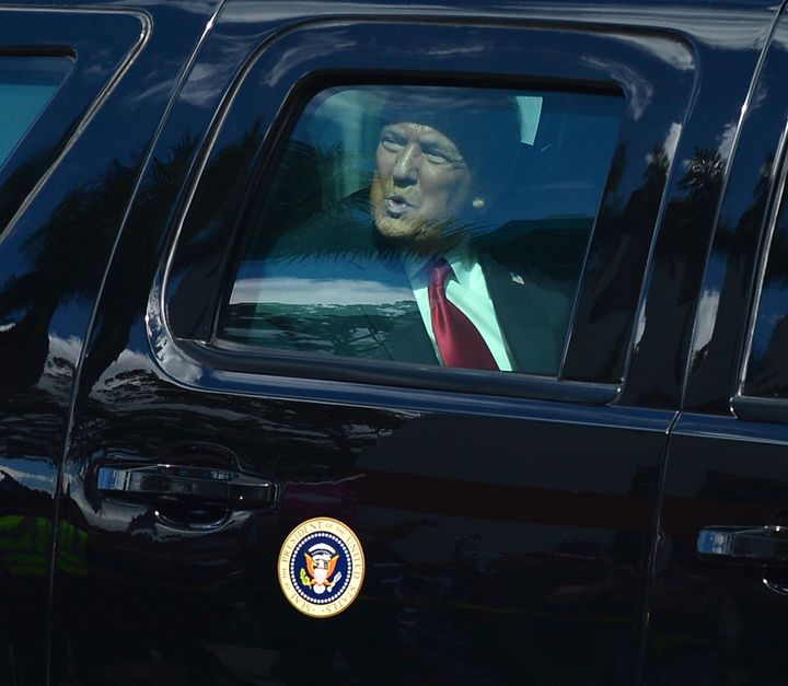 Donald Trump waves to supporters from his presidential motorcade after landing at Palm Beach International Airport on the way