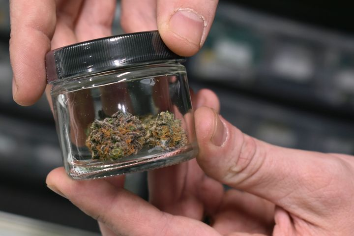 A worker holds up a jar with marijuana offered for sale at Montana Advanced Caregivers, a medical marijuana dispensary, in Bi