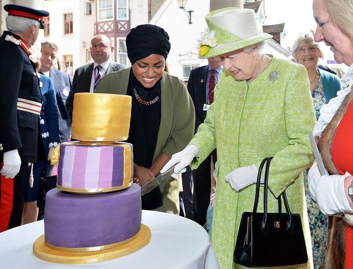 Queen Elizabeth II cuts into a birthday cake baked by Nadiya Hussain, left, during the queen's 90th birthday celebration in W