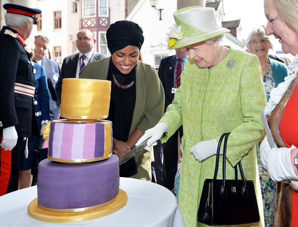 Queen Elizabeth II cuts into a birthday cake baked by Nadiya Hussain, left, during the queen's 90th birthday...
