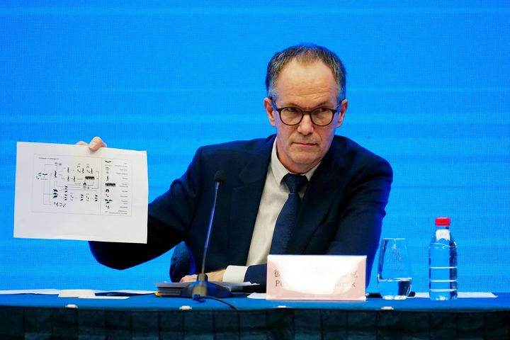 Peter Ben Embarek, a member of the WHO team tasked with investigating the origins of COVID-19, holds up a document Tuesday in Wuhan, China.