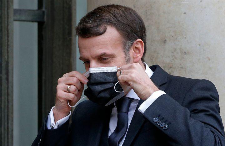 Macron, fotografiado mientras se coloca la mascarilla