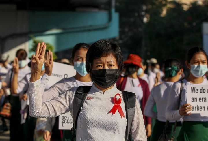 School teachers dressed in their school uniforms flash three-finger salute, a symbol of resistance during a protest in Yangon