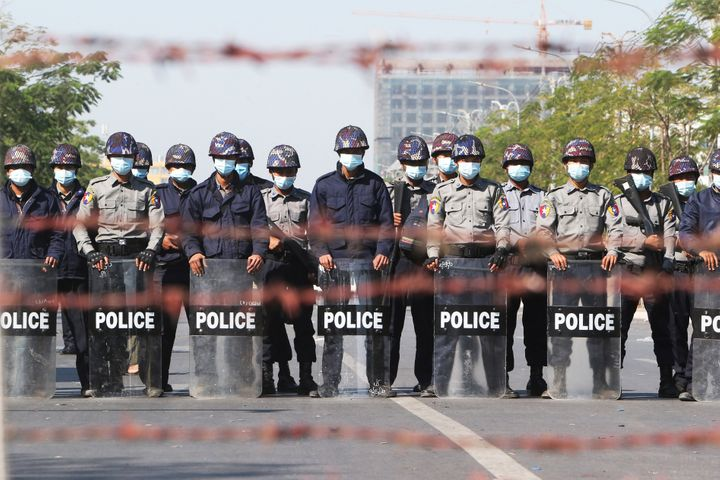 Police officers stand in a road blocking protesters during a demonstration in Mandalay, Myanmar, on Feb. 9, 2021. Protesters