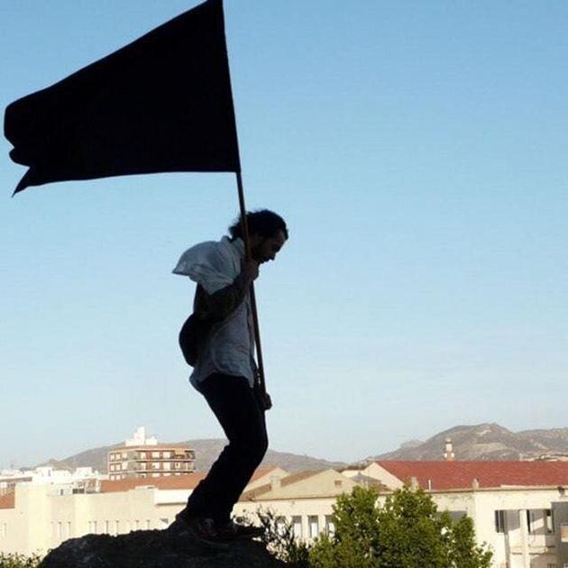 Mario Gutiérrez sosteniendo una bandera negra en el festival Abierto de Acción en
