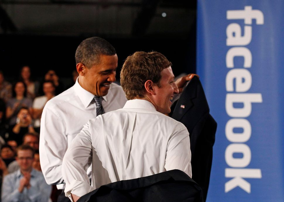U.S. President Barack Obama takes off his jacket as he attends a town-hall meeting at Facebook headquarters...