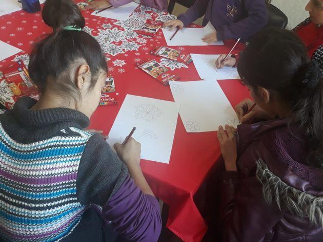 チョコレートのパッケージの絵を描くシリア難民の子どもたち