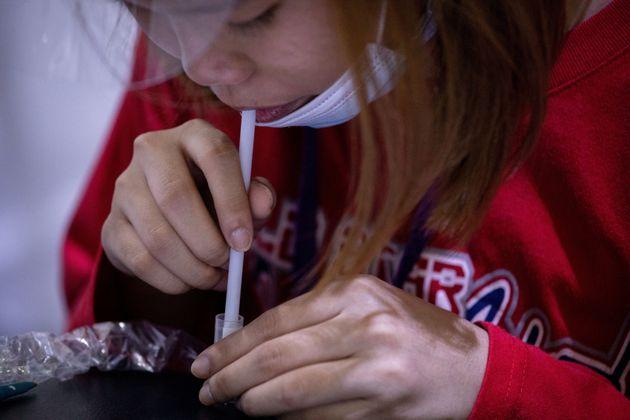 Une femme aux Philippines réalise un test salivaire pour le