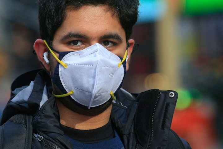 "A man wears two face masks in New York City on Dec. 10, 2020. The CDC says people can wear a cloth mask on top of a disposable surgical mask ""for better fit and extra protection."""