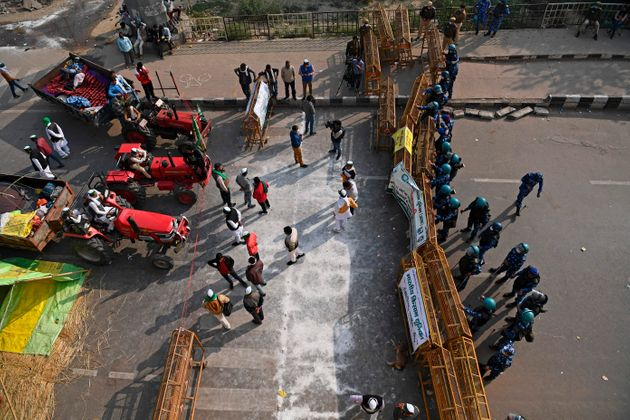 Indian farmers gather next to their tractors as police stand guard at a road block to stop them from...