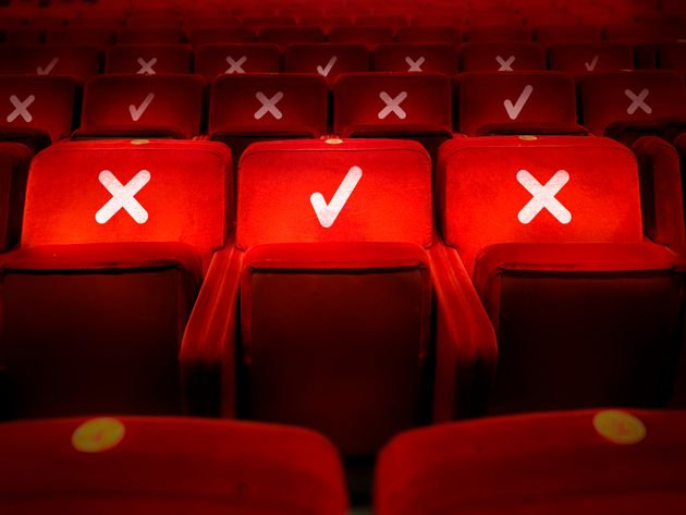 rows of empty chairs in a theater with the indication of where it is possible to sit to maintain the...