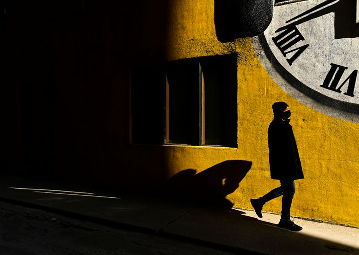 A man wearing a protective mask walks into the sunlight in Toronto on Feb. 11, 2021.