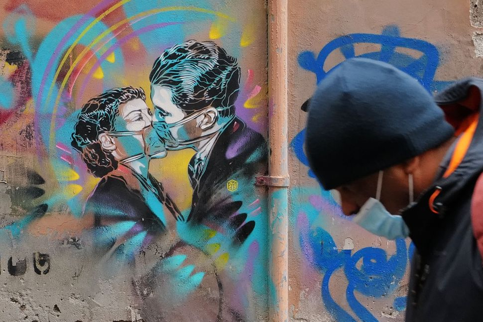 A pedestrian wearing a protective face mask walks past graffiti depicting a couple kissing wearing protective masks, in centr
