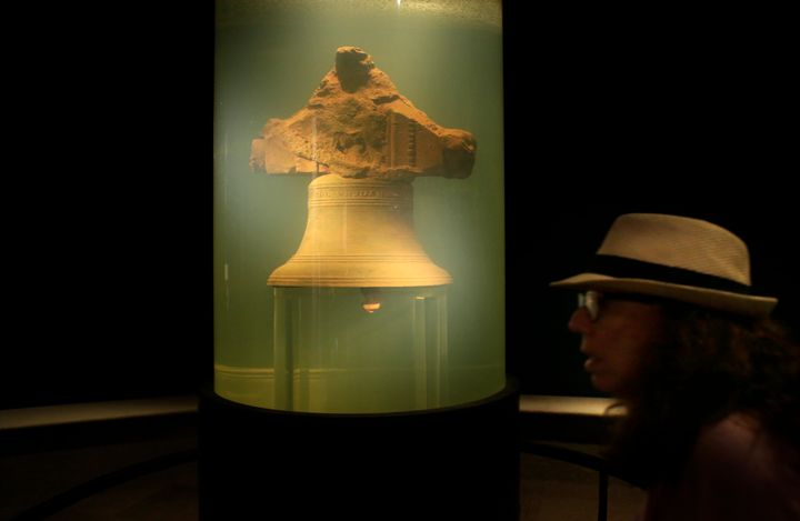 In this 2016 file photo, a museum visitor walks by a display of a bell once belonging to the pirate ship Whydah Gally at the