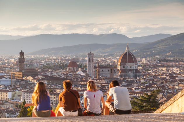 People watch the sunset from the steps of San Miniato al Monte over the city of Florence and the Basilica...