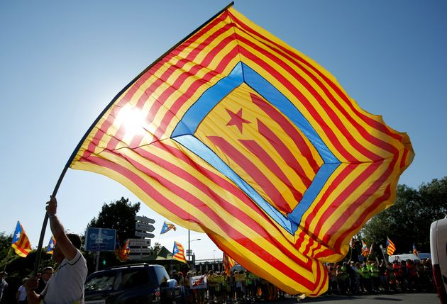 A protester flies the Catalan separatist flag during a rally in front of Parliament ...