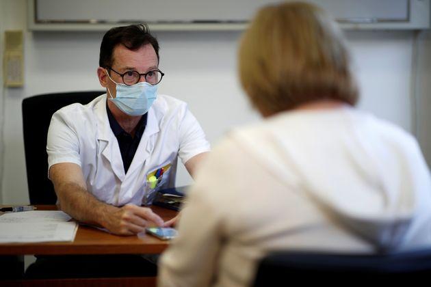 Un médecin ausculte une patiente souffrant des symptômes du Covid-19 depuis des mois à...