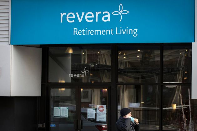 A person wears a mask while walking past a Revera retirement home in Kingston, Ont. on Dec. 8, 2020....
