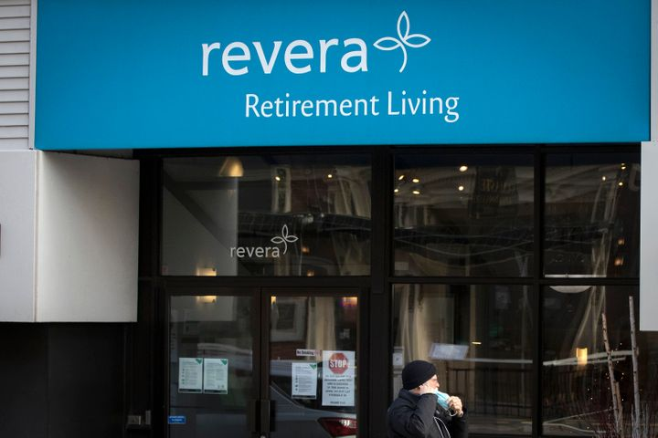 A person wears a mask while walking past a Revera retirement home in Kingston, Ont. on Dec. 8, 2020. The company, which is owned by a Canadian crown corporation, is being accused of aggressive but legal tax avoidance in the United Kingdom.