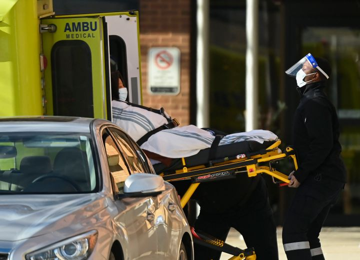 Paramedics take away a person from Revera Westside Long Term Care Home in Toronto during an outbreak of COVID-19 on Dec. 7, 2020.